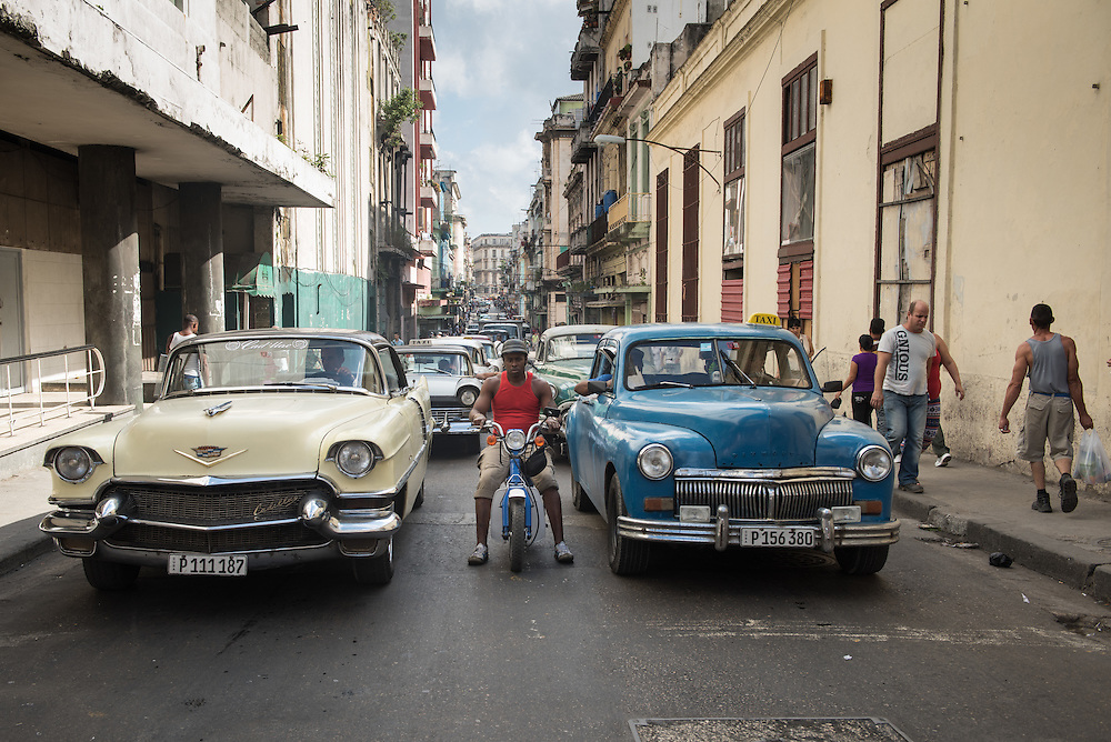 A Cadilac and a Plymouth, lead the pack of many other old American cars cars leftover form the 1950's at a stoplight in the Central Havana neighborhood of Havana, Cuba January 6, 2015. The United States announced last month that it will end its fifty-year trade embargo with Cuba and move to normalizing relations. Cuba's budding private sector is strengthening, but still has a long way to go to prepare for the expected stream of tourists. Photo Ken Cedeno