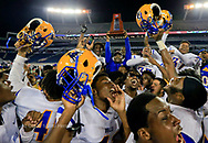 Northwest High School Bulls celebrate their  Class 6A football championship as coach Max Edwards raises the State championship trophy at Camping World Stadium in Orlando on Friday, December 8, 2017.