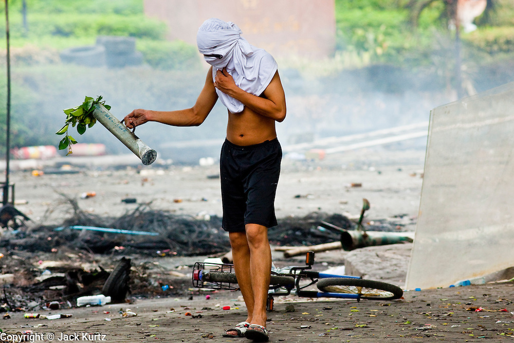 18 MAY 2010 - BANGKOK, THAILAND: A teenager sets out home made explosive device at Din Daeng Intersection in Bangkok Tuesday. The bomb did not go off. The intersection has been under periodic sniper fire from unidentified snipers near Thai military lines. Violent unrest continued in Bangkok again Tuesday nearly a week after Thai troops started firing on protesters and Bangkok residents took to the streets in violent protest against the government. Tuesday was not as violent as previous days however. Although protesters continued to set up roadblocks and flaming tire barricades across parts of the city, there was not as much gunfire from the government lines. The most active protesters were at the Din Daeng Intersection about a mile from the Red Shirts' Ratchaprasong camp.  PHOTO BY JACK KURTZ