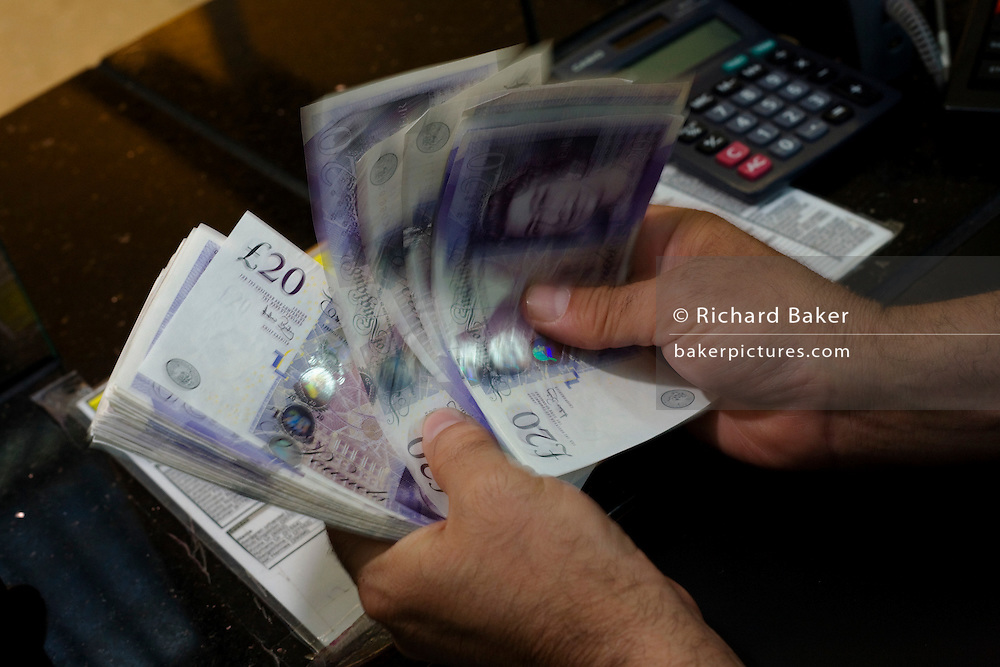 An assistant counts through blurred Pounds Sterling notes at the Travelex bureau de change at Heathrow Airport's Terminal 5.