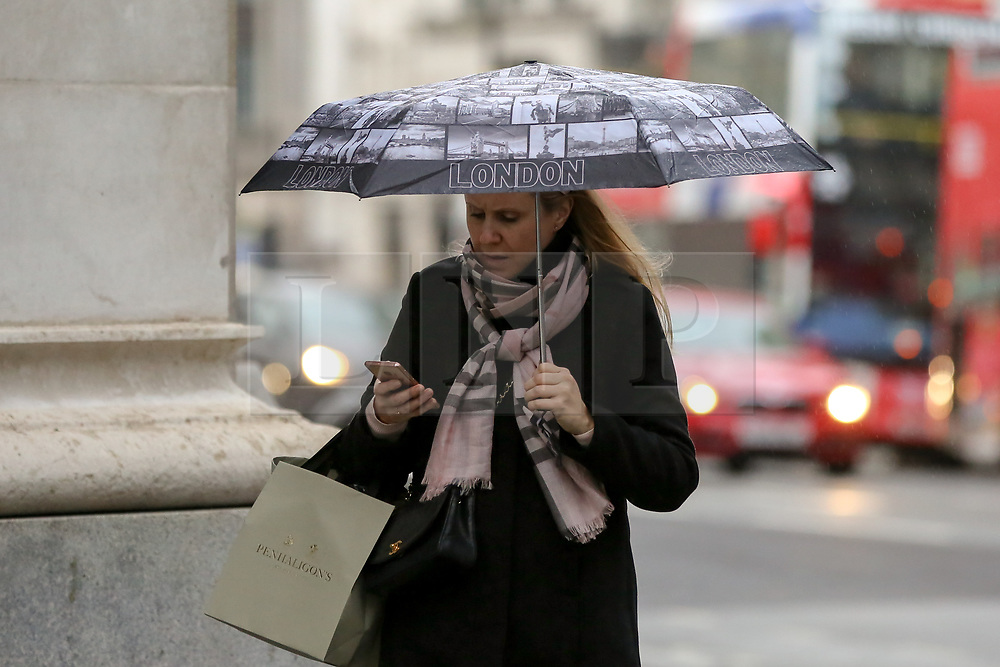 """© Licensed to London News Pictures. 8/112/2018. London, UK. A woman with a """"London"""" umbrella during rain and wet weather in Trafalgar Square. Photo credit: Dinendra Haria/LNP"""