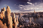 Tufa towers in Mono Lake at sunrise. Mono Lake lies near the town of Lee Vining. It is at least 700,000 years old and one of the oldest continuously existing lakes on the continent. Tufa towers (photographed) are made from calcium and carbonate combine to form limestone, which builds up over time around the lake bottom spring openings. Declining lake levels have exposed the tufa towers we see today. Some of the tufa towers are up to 30 feet high. Route 395: Eastern Sierra Nevada Mountains of California.