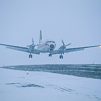 AVIATION. Commercial propellor plane lands in stormy white-out at Clyde River, Baffin Island, Nunavut, Canada.