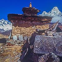 Mounts Everest, Lhotse and Ama Dablam rise behind a Tibetan Buddhist Chorten and mani (prayer) stones in the Khumbu region of Nepal's Himalaya.