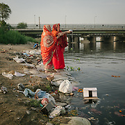 Hindu come to offer prayers at the polluted Yamuna river next to ITO bridge.