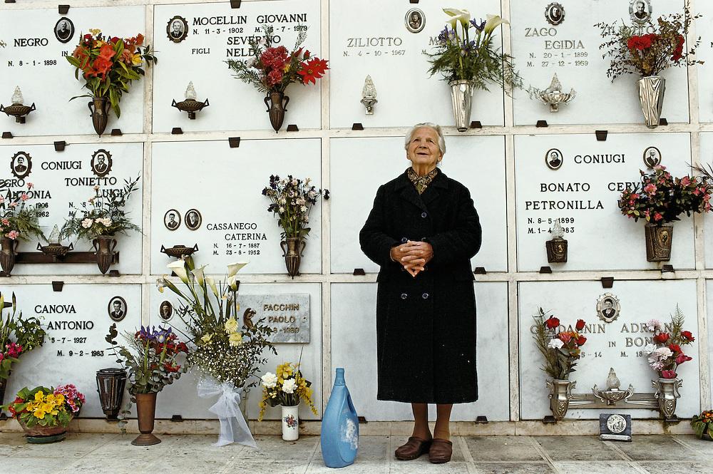 A peaceful old woman, standing in front of the tomb she will ocupy after death.