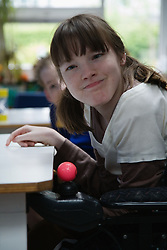 Physically disabled girl in supportive seat,
