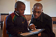 A young African school child reads green numbers that he can read on an orange plate from a black book, shown to him by a male optician in a class room in Zonnebloem School, Cape Town, South Africa.  The book is called the Ishara eye test and is a basic check for colour-blind.  The optician works for Mullers, who volunteer their staff to visit schools and perform eye tests on all children in school grade 2.