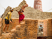 09 MARCH 2017 - BAGMATI, NEPAL: Workers carry unbaked bricks into a kiln at a brick factory in Bagmati, near Bhaktapur. There are almost 50 brick factories in the valley near Bagmati. The brick makers are very busy making bricks for the reconstruction of Kathmandu, Bhaktapur and other cities in the Kathmandu valley that were badly damaged by the 2015 Nepal Earthquake. The brick factories have been in the Bagmati area for centuries because the local clay is a popular raw material for the bricks. Most of the workers in the brick factories are migrant workers from southern Nepal.           PHOTO BY JACK KURTZ