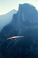 A hang glider soars above Yosemite valley on a clear summer day.  Hang gliding is regulated by park rangers and only allowed on certain days of the week.