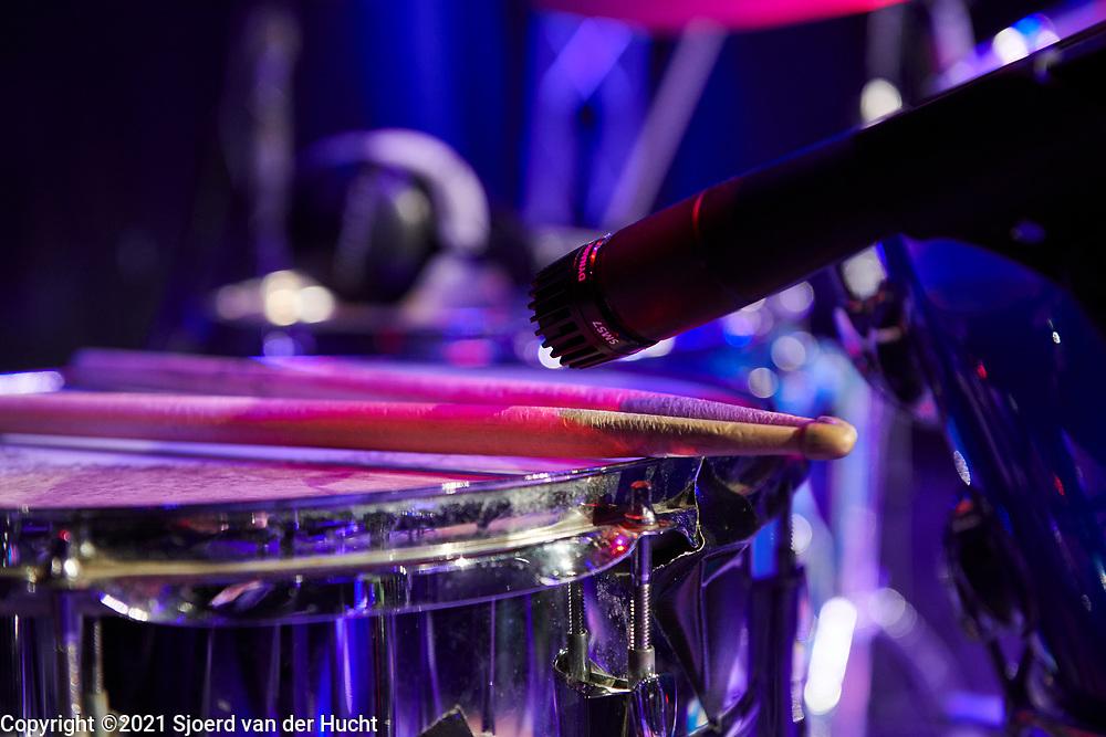 Klaar voor een optreden, drumsticks op een drumstel met microfoon. | Ready for a performance, drumsticks on a drum kit with microphone.