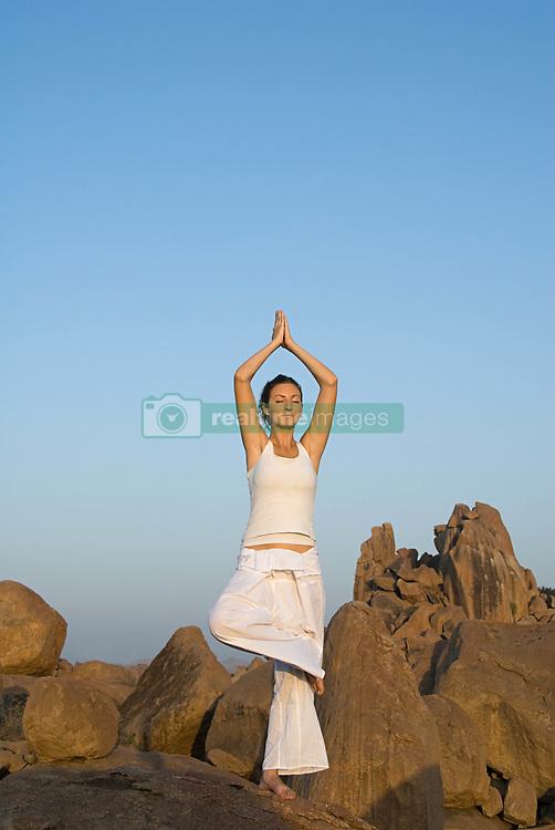 Jul. 26, 2012 - Woman in yoga pose by rocks (Credit Image: © Image Source/ZUMAPRESS.com)