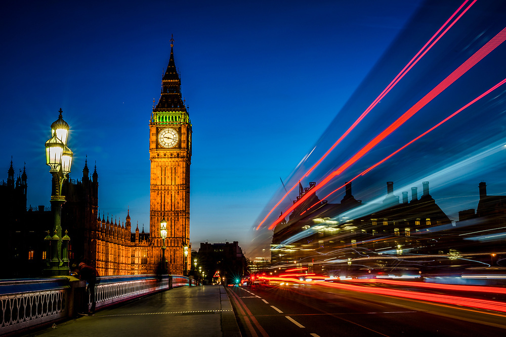 Long exposure image of the Elizabeth Tower taken from the Westminster Bridge during the Blue Hour. The lights of the iconic London red buses are shown as light trails.