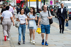 © Licensed to London News Pictures. 27/07/2021. LONDON, UK.  People out shopping in Regent Street.  According to new analyis by Huq Industries, a mobility research business, the UK's Covid app 'pingdemic' is leading to a significant slowdown in people both moving around and visiting shops. Across the UK as a whole in July, average retail footfall has fallen by 2.83% and mobility by 5.5%.  Photo credit: Stephen Chung/LNP
