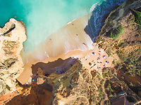 Aerial photography of Pinhão Beach surrounded by cliffs in Lagos, Portugal.
