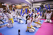 """Students celebrate after watching Japan's Ryo Kiyuna winning over Spain's Damian Quintero after the men's kata final bout of the karate competition during the Tokyo 2020 Olympic Games on TV at a """"dojo"""" of Kenkojuku Budokan karate school in Hachioji area of Tokyo on August 6, 2021. (Photo by Yuki IWAMURA / AFP)"""