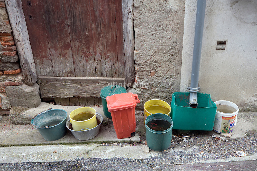 several buckets at a roof drain pipe to collect the rainwater