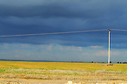 Environmental concept. Harvested fields and electric cables with dramatic sky
