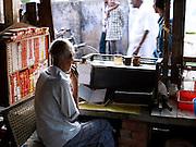Shopkeeper selling cigarettes in a roadside cafe, Kerala, India