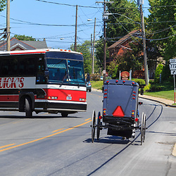 Intercourse, PA - June 12, 2016: A Horse-drawn Amish buggy shares the village road with a tour bus  in Lancaster County.