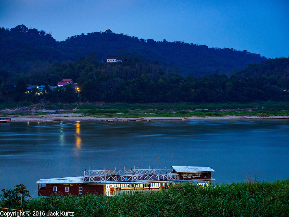 """12 MARCH 2016 - LUANG PRABANG, LAOS:  A tourist cruise boat parked on the banks of the Mekong River in Luang Prabang. Luang Prabang was named a UNESCO World Heritage Site in 1995. The move saved the city's colonial architecture but the explosion of mass tourism has taken a toll on the city's soul. According to one recent study, a small plot of land that sold for $8,000 three years ago now goes for $120,000. Many longtime residents are selling their homes and moving to small developments around the city. The old homes are then converted to guesthouses, restaurants and spas. The city is famous for the morning """"tak bat,"""" or monks' morning alms rounds. Every morning hundreds of Buddhist monks come out before dawn and walk in a silent procession through the city accepting alms from residents. Now, most of the people presenting alms to the monks are tourists, since so many Lao people have moved outside of the city center. About 50,000 people are thought to live in the Luang Prabang area, the city received more than 530,000 tourists in 2014.      PHOTO BY JACK KURTZ"""