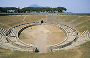 The Amphitheatre of Pompeii is the oldest surviving Roman amphitheatre. It hosted gladiatorial games and other events. Seating was divided into three distinct social groupings and protection from the sun was provided by velaria suspended above the crowd from the top of the arena. The amphitheatre was buried by the eruption of Vesuvius (visible behind) in 79 AD. Pompeii, Italy, 2001