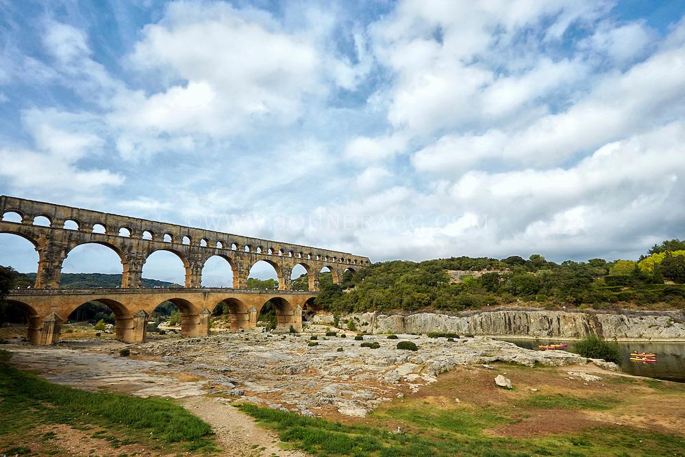 View of Pont du Gard (Roman Aqueduct), kayakers floating down the Gardon River, and Garrigue Natural Area, Vers-Pont-du-Gard, France.