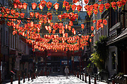 Lanterns hanging from above Gerrard Street in Chinatown, Soho which is almost deserted due to the Covid-19 outbreak social distancing on what would normally be a busy, bustling day with hoards of people out to shop and socialise on 22nd March 2020 in London, England, United Kingdom. Coronavirus or Covid-19 is a new respiratory illness that has not previously been seen in humans. While much or Europe has been placed into lockdown, the UK government has announced more stringent rules as part of their long term strategy, and in particular social distancing.
