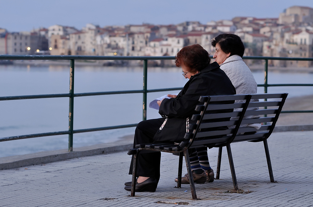 Women on a bench overlooking the ocean in the historic town of Cefalu on the coast of Sicily, Italy.
