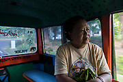 Ibu Kum, age 60, traveling to the local farmers market in Downtown Surabaya. Ibu Kum is one of several service workers (pembantu) that work for expats in the suburbs of Surabaya. She has been working as a nanny, housekeeper and cook in the expat community for over 30 years. Surabaya, Indonesia.