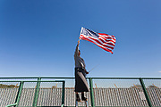A female military aircraft enthusiast waves an American flag at a passing United States Airforce plane from a park at the end of Naval Air Facility, Atsugi airbase near  Yamato, Kanagawa, Japan. Thursday April 11th 2019