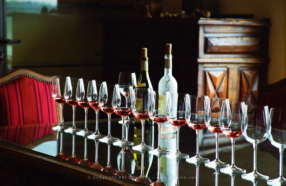 A row of glasses filled with rose wine and two bottles on a reflective table top in the tasting room, Chateau Puech-Haut, Saint-Drezery, Coteaux du Languedoc, Languedoc-Roussillon, France