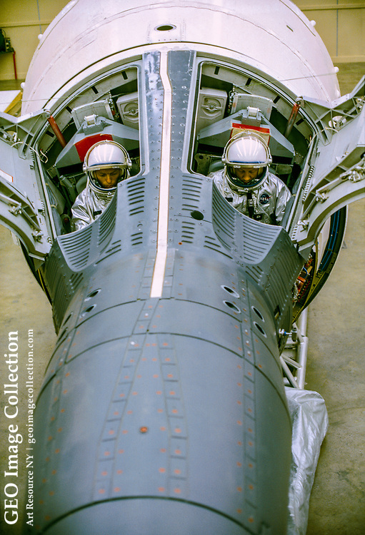 View of two pressure-suited test subject in a Gemini capsule with hatches.