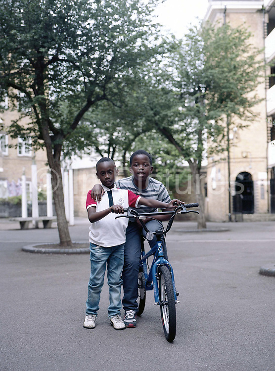 Two children with a BMX at Somers Town on 1st July 2016 in London, United Kingdom. Somers Town, a district in north west London, is a large housing estate nestled between Euston, St Pancras and Kings Cross Library. Predominantly filled with social housing for the past 200 years, much of the area's housing was built in the twentieth century by the local authority.