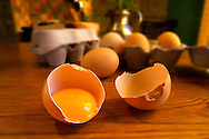 Free range eggs, one cracked with a yoke, in a coutry kitchen setting