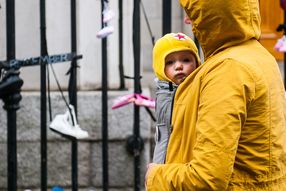 """Dublin, Ireland. 26th August, 2018. <br /> A children and his mother prepare the symbols of the protest, babyshoes, on the gate of St. Mary Pro Cathedral, in Marlborough Street just ahead the Mass during the second of the two-days of the visit of Pope Francis in Dublin, Ireland.<br /> Pope Francis has made a two-day visit to the Republic of Ireland by celebrating a Mass at Dublin's Phoenix Park. The Argentine Pope asked forgiveness for the """"abuses in Ireland, abuses of power, conscience and sexual abuses"""" perpetrated by Church leaders. It was the first papal visit to Ireland for 39 years. During his activities many activists, victims and survivors have made protests and a silent march Garden of Remembrance towards the last Magdalene Laundry to close in Ireland.<br />  © Simone Padovani"""