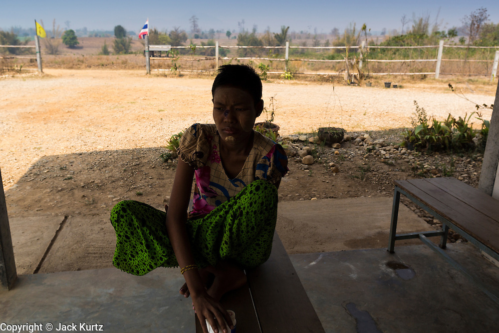 03 MARCH 2104 - MAE KASA, TAK, THAILAND: A patient sits on the front porch of the clinic at the Sanatorium Center for Border Communities in Mae Kasa, about 30 minutes north of Mae Sot, Thailand. The Sanatorium provides treatment and housing for people with tuberculosis in an isolated setting for about 68 patients, all Burmese. The clinic is operated by the Shoklo Malaria Research Unit and works with several other NGOs that assist Burmese people in Thailand. Reforms in Myanmar have alllowed NGOs to operate in Myanmar, as a result many NGOs are shifting resources to operations in Myanmar, leaving Burmese migrants and refugees in Thailand vulnerable. Funding cuts could jeopardize programs at the clinic. TB is a serious health challenge in Burma, which has one of the highest rates of TB in the world. The TB rate in Thailand is ¼ to ⅕ the rate in Burma.        PHOTO BY JACK KURTZ