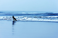 A surfer walks with his surfboard on the beach in Essaouira.