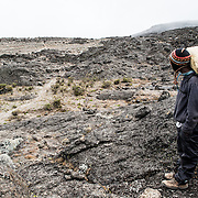 A porters stops for a moment to rest on the trail between Moir Hut Camp (13,660 feet) and Lava Tower (15,215 feet) on Mt Kilimanjaro's Lemosho Route. At this elevation, the heath zone (moorland) gives way to rocky alpine desert.