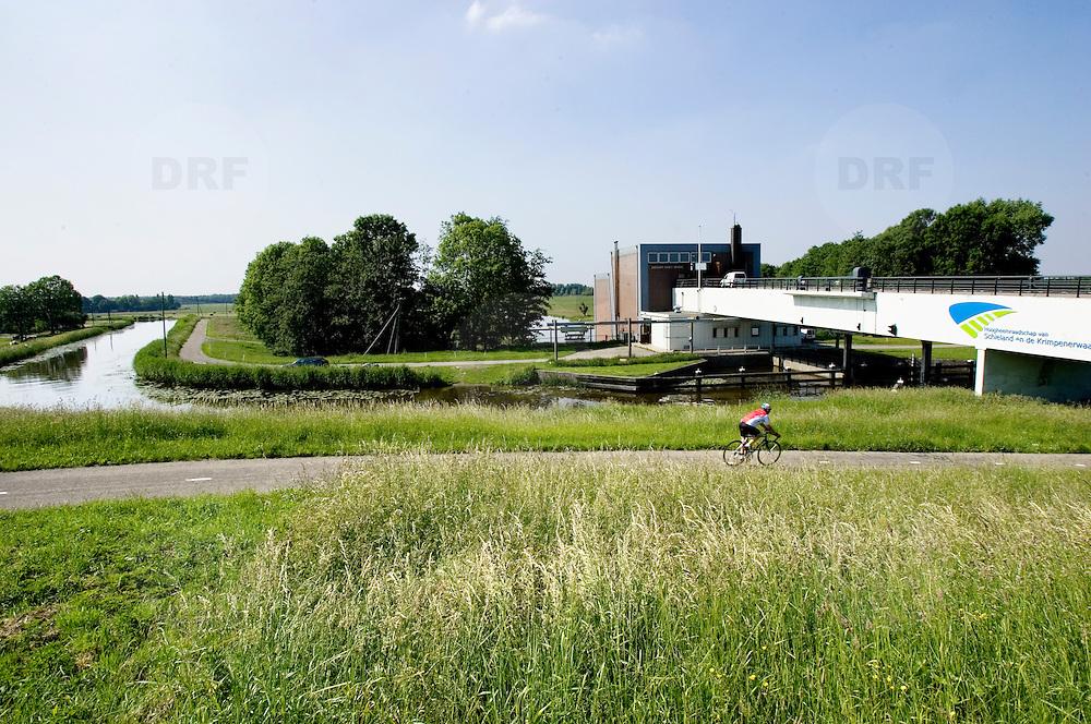 Nederland Moordrecht 24 mei 2007 20070524..Wielrenner met op de achtergrond het gemaal de Abraham Kroes..Serie tbv Schieland en de Krimpenerwaard, deze zorgt als waterschap voor droge voeten en schoon water in een bepaald gebied. Het beheersgebied van Schieland en de Krimpenerwaard strekt zich uit tussen Rotterdam, Schoonhoven en Zoetermeer. Binnen dit gebied zorgt Schieland en de Krimpenerwaard voor de kwaliteit van het oppervlaktewater, het waterpeil en de waterkeringen. Daarnaast beheert Schieland en de Krimpenerwaard een aantal wegen in de Krimpenerwaard...Foto David Rozing