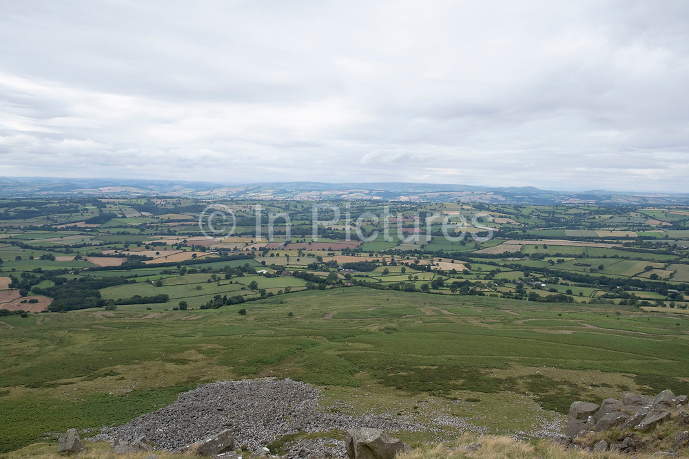 View from Titterstone Clee Hill on 22nd July 2020 in Cleedownton, United Kingdom. Titterstone Clee Hill, sometimes referred to as Titterstone Clee or, incorrectly, Clee Hill, is a prominent hill in the rural English county of Shropshire, rising at the summit to 533 metres above sea level. It is one of the Clee Hills, in the Shropshire Hills Area of Outstanding Natural Beauty. Most of the summit of the hill is affected by man-made activity, the result of hill fort construction during the Bronze and Iron Ages and, more recently, by years of mining for coal and quarrying for dolerite, known locally as dhustone, for use in road-building. Many derelict quarry buildings scattered over the hill are of industrial archaeological interest as very early examples of the use of reinforced concrete. Several radar domes and towers operate on the summit of the hill. The largest of the radar arrays is part of the National Air Traffic Services NATS radar network, and covers one of 30 overlapping regions of UK airspace. The one on Titterstone Clee monitors all aircraft within a 100-mile radius.