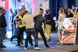 © Licensed to London News Pictures . 15/06/2014 . Manchester , UK . Two men fight outside a takeaway . People on a night out in Manchester City Centre overnight , following England's defeat to Italy in the World Cup . Photo credit : Joel Goodman/LNP