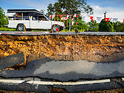 14 JULY 2015 - THAILAND:  A pickup truck is driven along a collapsed roadbed in Ayutthaya province. The drought that has crippled agriculture in central Thailand is now impacting residential areas near Bangkok. The Thai government is reporting that more than 250,000 homes in the provinces surrounding Bangkok have had their domestic water cut because the canals that supply water to local treatment plants were too low to feed the plants. Local government agencies and the Thai army are trucking water to impacted communities and homes. Roads in the area have started collapsing because of subsidence caused by the retreating waters. Central Thailand is contending with drought. By one estimate, about 80 percent of Thailand's agricultural land is in drought like conditions and farmers have been told to stop planting new acreage of rice, the area's principal cash crop.      PHOTO BY JACK KURTZ