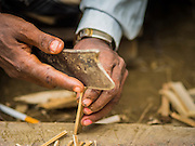 07 NOVEMBER 2014 - SITTWE, RAKHINE, MYANMAR: A detail photo of a Rohingya Muslim man splitting sticks to make ice cream bars in front of his hut in an IDP camp for Rohingya. After sectarian violence devastated Rohingya communities and left hundreds of Rohingya dead in 2012, the government of Myanmar forced more than 140,000 Rohingya Muslims who used to live in and around Sittwe, Myanmar, into squalid Internal Displaced Persons camps. The government says the Rohingya are not Burmese citizens, that they are illegal immigrants from Bangladesh. The Bangladesh government says the Rohingya are Burmese and the Rohingya insist that they have lived in Burma for generations. The camps are about 20 minutes from Sittwe but the Rohingya who live in the camps are not allowed to leave without government permission. They are not allowed to work outside the camps, they are not allowed to go to Sittwe to use the hospital, go to school or do business. The camps have no electricity. Water is delivered through community wells. There are small schools funded by NOGs in the camps and a few private clinics but medical care is costly and not reliable.   PHOTO BY JACK KURTZ