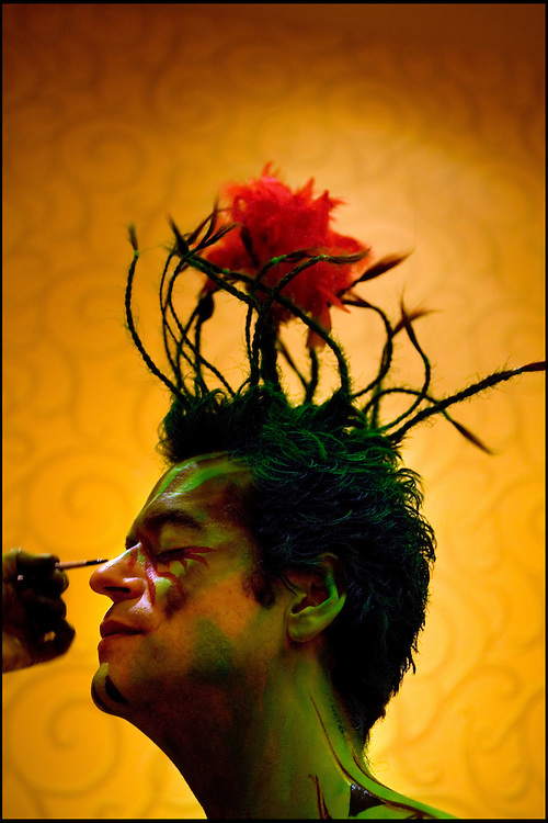 .Artist Benita Brennan applies green paint to Cliff Matthews' face during a body-painting jam at the Embassy Suites on Friday. Matthews' floral top-knot was contributed by hairstylist Lorenzo Colorado. The jam, in which artists used the bodies of volunteer models as living canvases, is part of the U.S. Body Painting Competition that continues through Sunday.