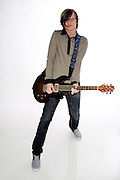 Young male Caucasian in his early 20s in black jeans playing an electric guitar full body shot. MR