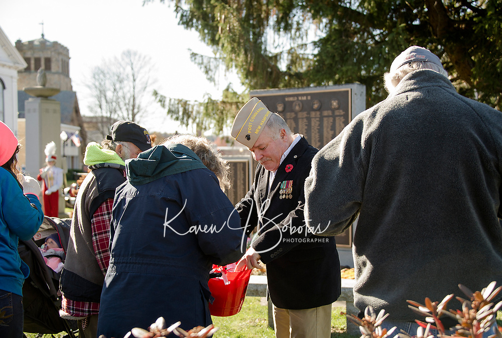 """VFW Commander Timm Grant hands out """"Buddy Poppy's"""" to folks gathered at Veteran's Square for the Veteran's Day services on Sunday morning.  (Karen Bobotas/for the Laconia Daily Sun)"""
