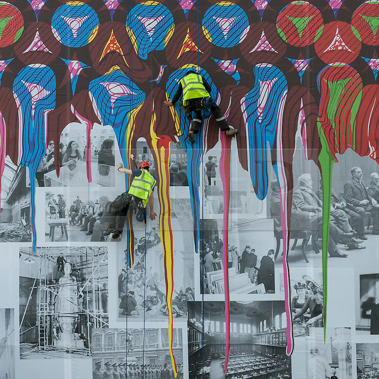 """© Licensed to London News Pictures. 16/05/2016. London, UK. A specialist team of abseilers hang down the façade of the Royal Academy of Arts' Burlington Gardens building in Mayfair, adding the final touches to a monumental public artwork called """"RA Family Album, 2016"""" by internationally renowned artist Yinka Shonibare RA.  The artwork covers the scaffolding on the façade as part of the RA's transformative redevelopment which will be completed in time for its 250th anniversary in 2018.  Photo credit : Stephen Chung/LNP"""