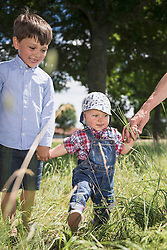 Small boy holding hand of his brother through a meadow in the countryside, Bavaria, Germany