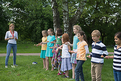 Group of children wait in a row to start the egg race, Munich, Bavaria, Germany